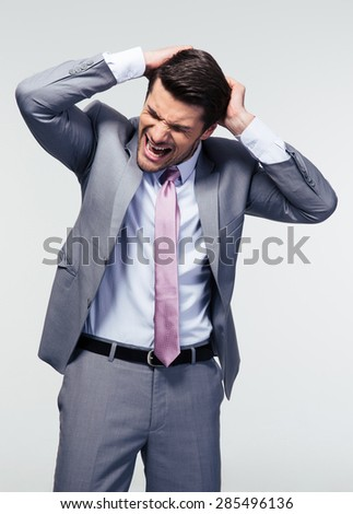 Portrait of a frustrated businessman over gray background - stock photo