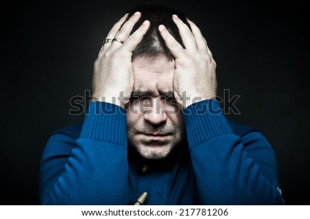 Portrait of a frustrated young man holding on to head - stock photo