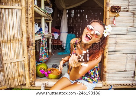portrait of a funny and beautiful young woman playing ukulele - stock photo
