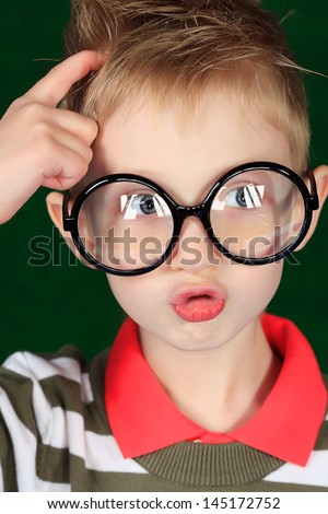 Portrait of a funny boy in big glasses thinking about something. - stock photo