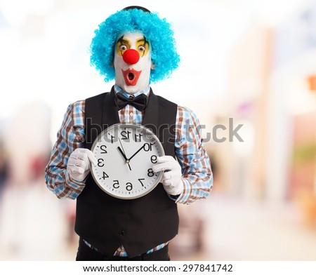 portrait of a funny clown holding a clock - stock photo
