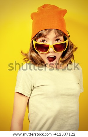 Portrait of a funny expressive teen girl over yellow background. - stock photo