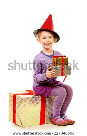 Portrait of a funny little girl sitting on a box with present and smiling at camera. Isolated over white. - stock photo