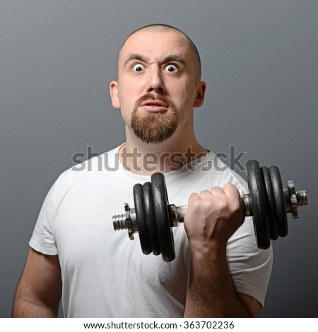 Portrait of a funny man holding dumbbells against gray background - stock photo
