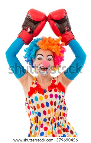 Portrait of a funny playful female clown in colorful wig and boxing gloves keeping hands up, looking at camera and smiling, isolated on a white background - stock photo