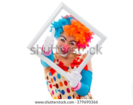 Portrait of a funny playful female clown in colorful wig holding a white frame, looking at camera and showing OK sign, isolated on a white background - stock photo