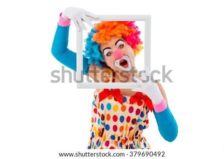 Portrait of a funny playful female clown in colorful wig holding a white frame, looking at camera and showing emotions, isolated on a white background - stock photo