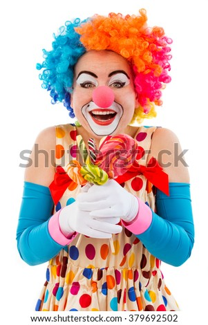 Portrait of a funny playful female clown in colorful wig holding lollipops, looking at camera and smiling, isolated on a white background - stock photo