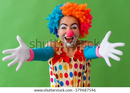 Portrait of a funny playful female clown in colorful wig stretching her hands like ready to hug and smiling, standing on a green background - stock photo