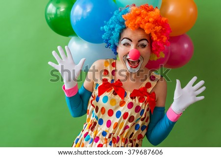 Portrait of a funny playful female clown in colorful wig teasng and showing palms, in the background balloons, standing on a green background - stock photo