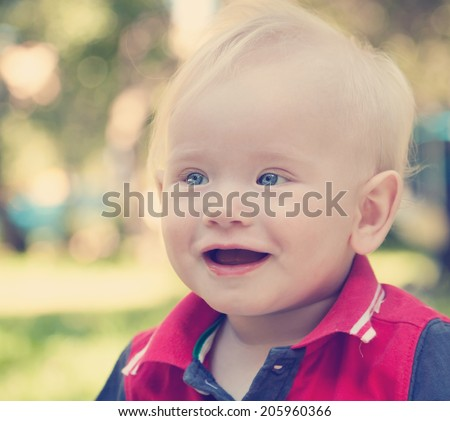 Portrait of a funny smiling year-old kid, in soft focus