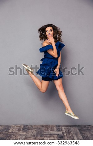 Portrait of a funny woman jumping and covering her mouth on gray background