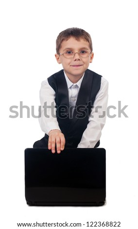 Portrait of a funny young boy dressed up in suit sitting on the floor and working with laptop, isolated on white background - stock photo