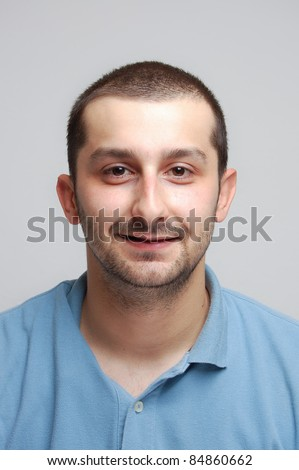 portrait of a funny young man, isolated on gray - copy space - stock photo