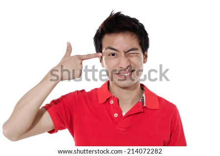 Portrait of a funny young man pointing finger gun gesture to head - stock photo