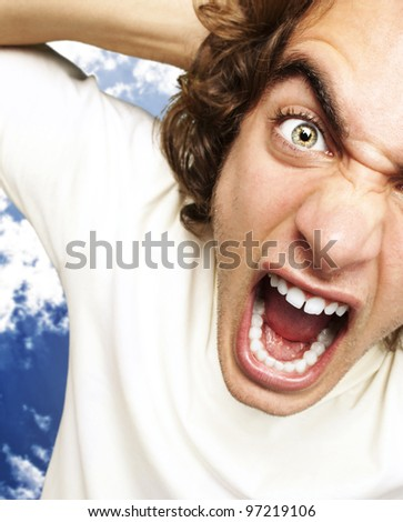 portrait of a furious young man shouting against a cloudy sky background - stock photo