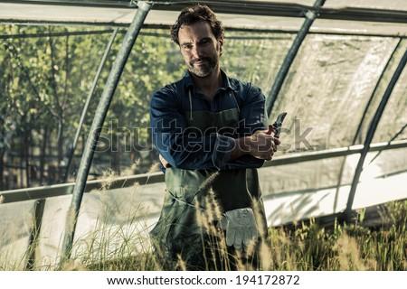 Portrait of a gardener inside a greenhouse - stock photo