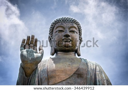 Portrait of a giant seated Buddha with a raised right hand - stock photo