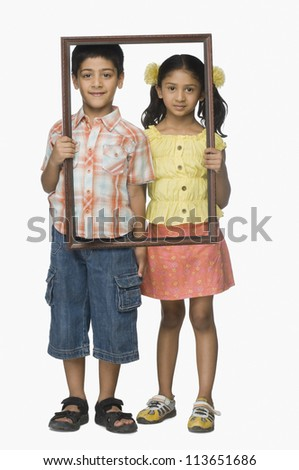 Portrait of a girl and a boy holding an empty picture frame