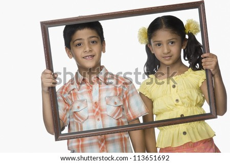 Portrait of a girl and a boy holding an empty picture frame - stock photo