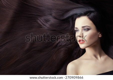 Portrait of a girl brunette closeup. She is lying on her long hair. Hair very much. - stock photo