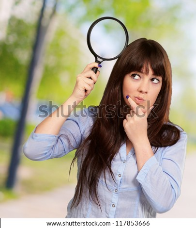 Portrait Of A Girl Holding A Magnifying Glass And Thinking, Outdoor