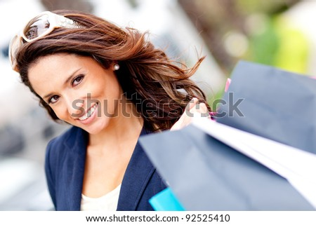 Portrait of a girl holding shopping bags and smiling - stock photo