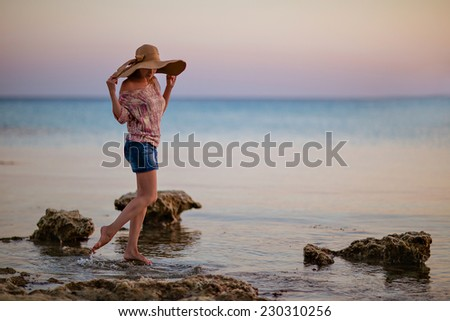Portrait of a girl in a broad-brimmed hat on the background of the sunset sea in Cyprus - stock photo