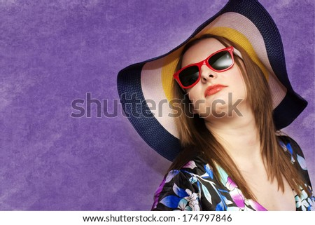 portrait of a girl in a hat on a blue background - stock photo
