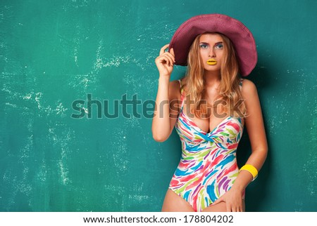 portrait of a girl in a hat, summer style, on green background - stock photo
