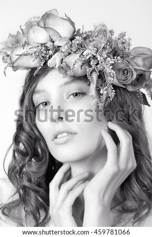 Portrait of a girl in a wreath of roses on a white background
