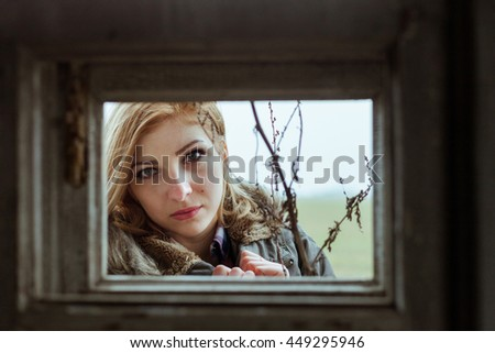 portrait of a girl in an old broken window - stock photo