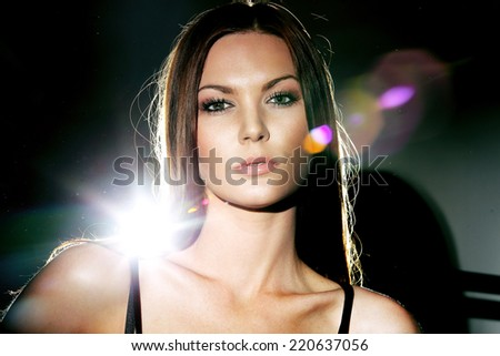 Portrait of a girl in bright light studio dark background - stock photo