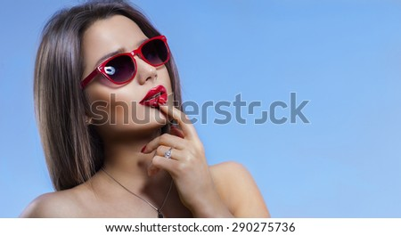 portrait of a girl in sunglasses on a blue background