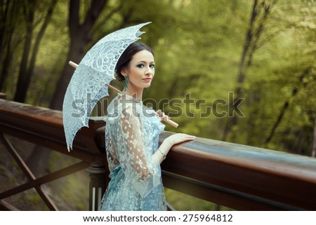 Portrait of a girl in the forest, her old-fashioned dress. In her hands she holds a vintage umbrella. - stock photo