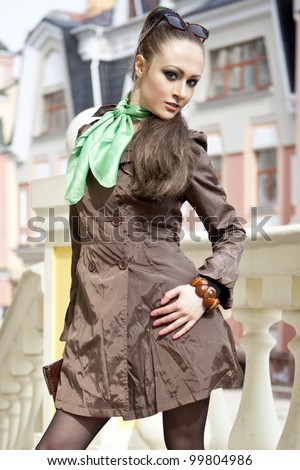 portrait of a girl in the street during the day against a background of houses - stock photo