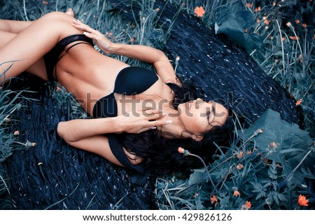 Portrait of a girl in underwear lying on the grass - stock photo