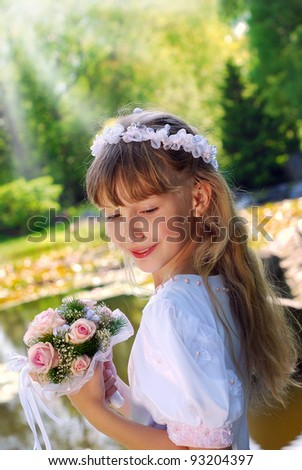 portrait of a girl in white dress and wreath ,going to the first holy communion and posing in the park - stock photo