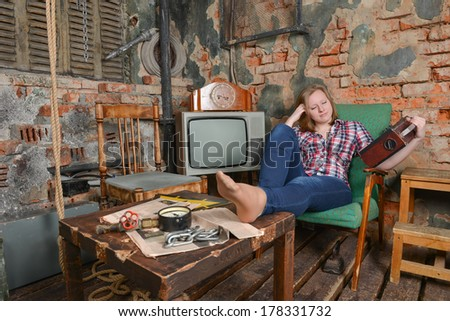 Portrait of a girl listening music in grunge interior - stock photo