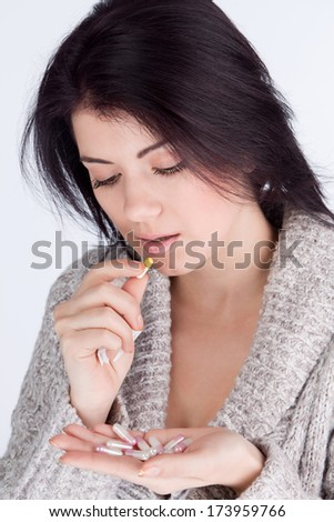 portrait of a girl looking at medicine and bed in the mouth capsule - stock photo