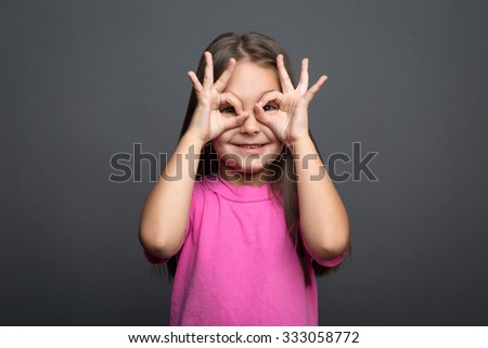 Portrait of a girl looking through her fingers - stock photo