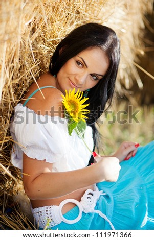 portrait of a girl next to haystack - stock photo