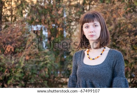 portrait of a girl on a background of autumn leaves - stock photo