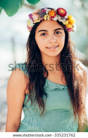 Portrait of a girl outdoors with a flower garland - stock photo