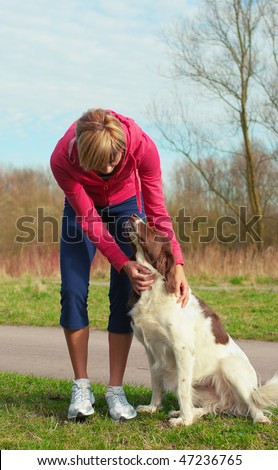 Portrait of a girl playing outdoors with a dog. - stock photo