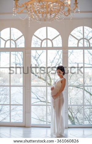 Portrait of a girl pregnant brunette in a white transparent dress in the interior decoration of the New Year and, standing against the huge window