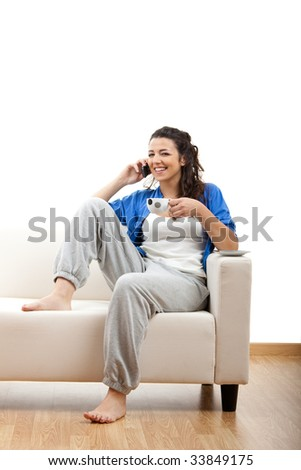 Portrait of a girl seated on the couch and making a phone call