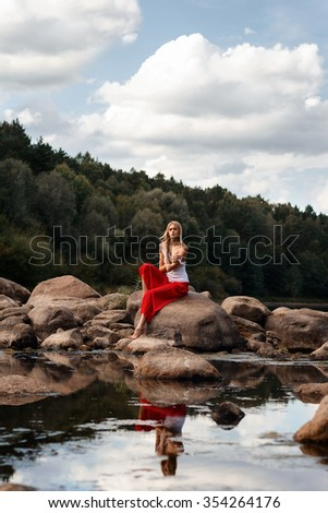 Portrait of a girl sitting on the stones near the river