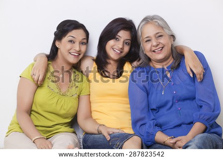 Portrait of a girl sitting with her mother and grandmother - stock photo