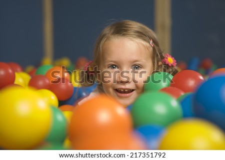 Portrait of a girl smiling in a ball pool - stock photo